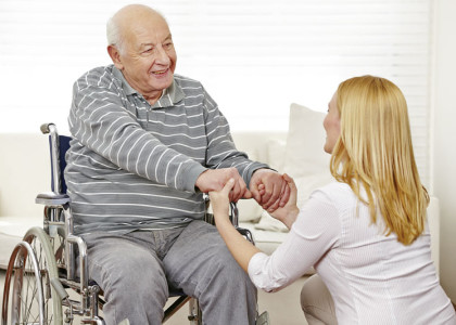 Frau hält die Hände von einem alten Mann im Rollstuhl im Pflegeheim